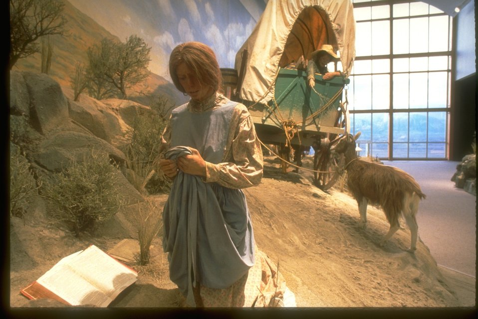 Early settlers on the Oregon Trail with a grieving woman reading the bible and in the background a young boy hanging out the covered wagon reaching to feed a goat.  Replica in the NHOTIC.