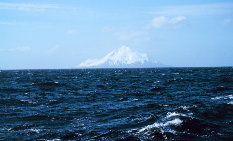 An Aleutian Island peak looms in the distance.