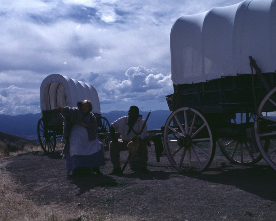 Nancy Harms and Dylan Prichertt portray pioneer woman and a black pioneer at an Oregon Trail wagon encampment.