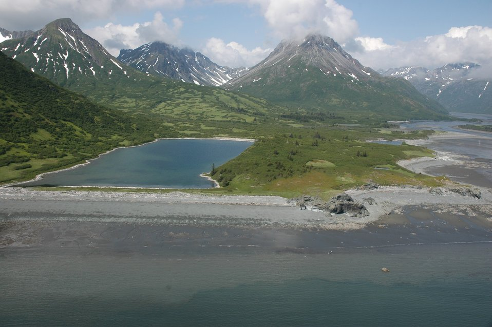 Aerial photograph. A rectangular lake, majestic mountains, the low tide line approximately 20 feet vertically below the logs and debris marking high tide.