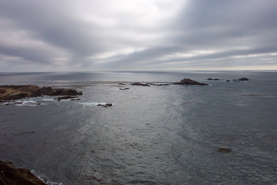 Gray clouds, black rock and a gray sea at Point Lobos State Reserve.