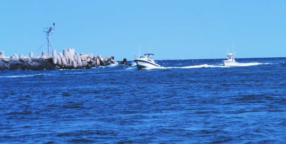 Recreational fishing boats passing the jetties at Manasquan Inlet