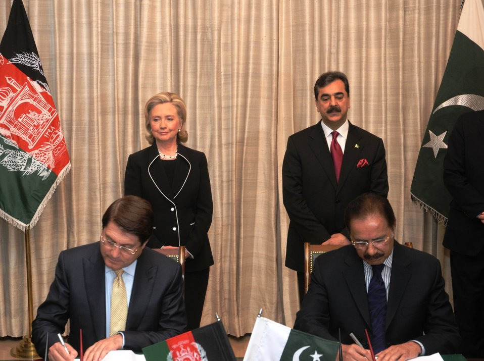 Secretary Clinton and Pakistani Prime Minister Yousaf Raza Gilani Watch Pakistani Federal Minister for Commerce Makhdoom Amin Faheem and Afghan Minister for Trade and Industries Dr. Anwarul Haq Sign a Pakistan-Afghanistan Transit Trade Agreement