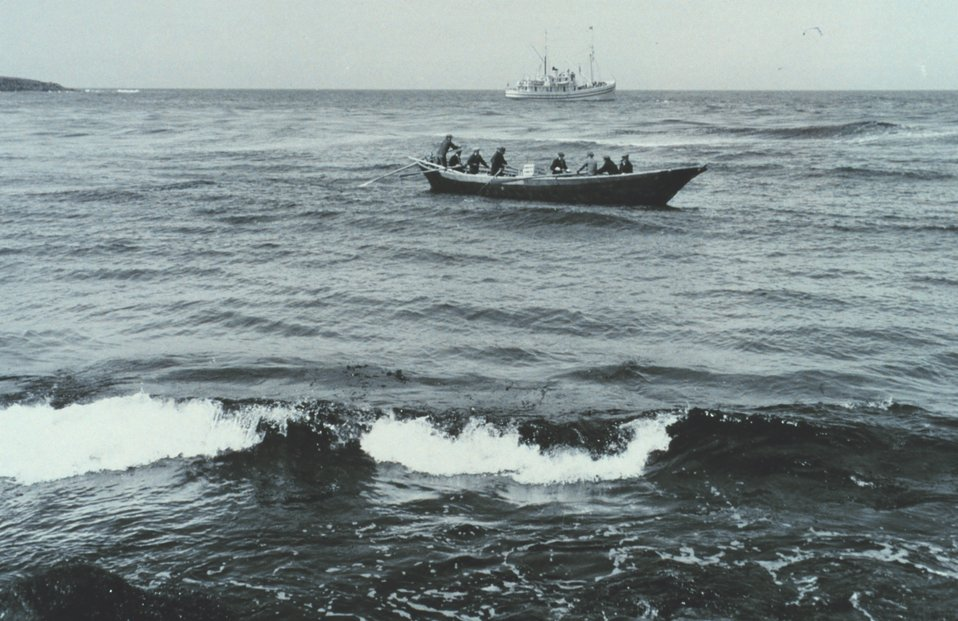 A bidarrah or large skin boat off St. George Island.  The Bureau of Commercial Fisheries vessel PENGUIN is in the background.  F&WS  10,030.