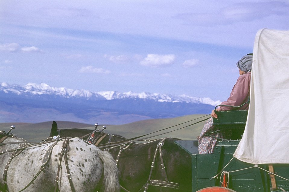 NHOTIC 10th Anniversary. Wagon train reenactment. Profile of woman pioneer with mountains in background.