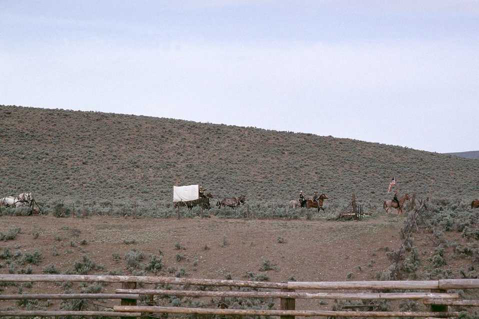 NHOTIC 10th Anniversary, wagon train reenactment. Far shot of covered wagons and pioneers on the Oregon Trail.
