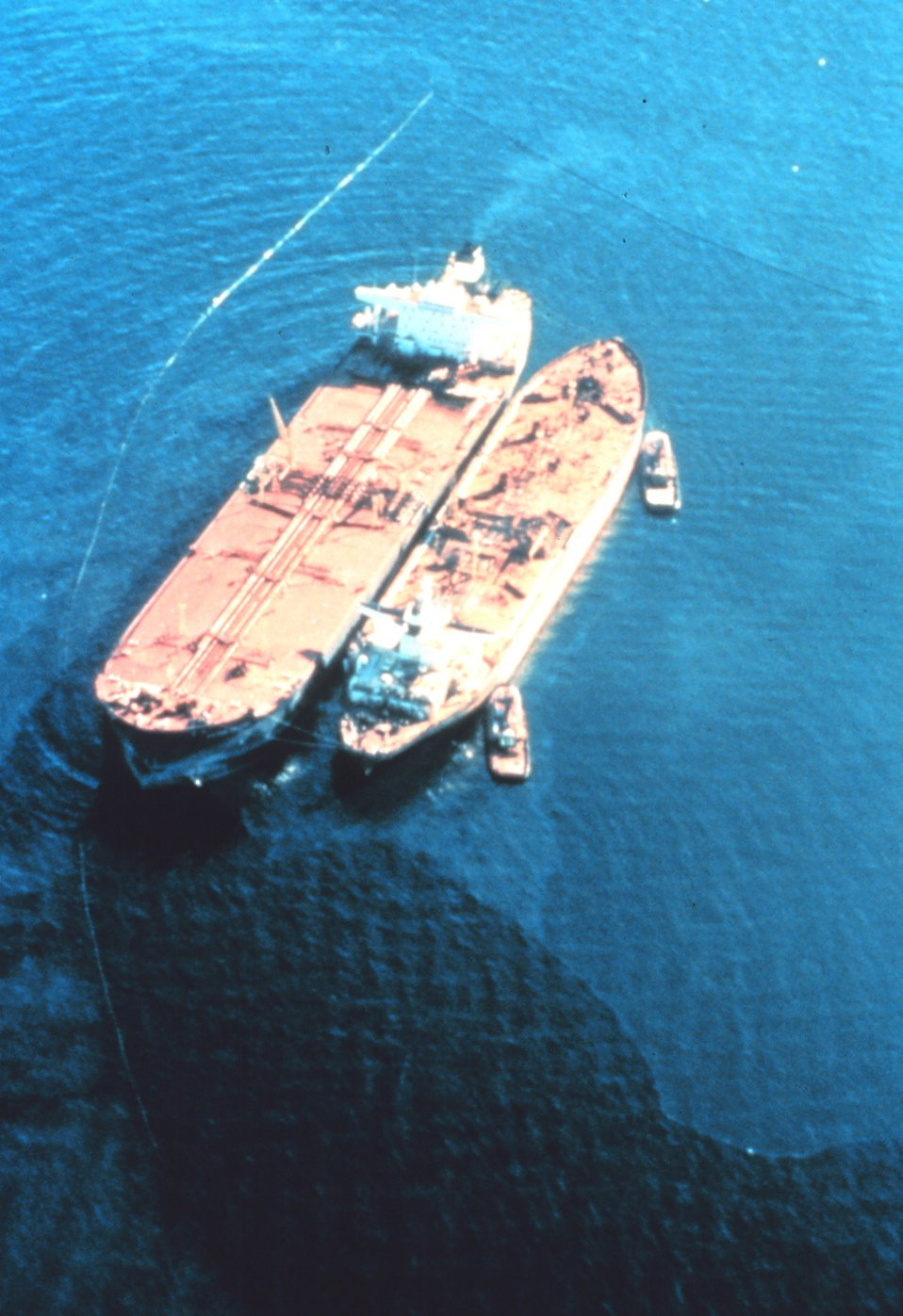 EXXON VALDEZ aground on Bligh Reef being lightered to reduce oil spillage and lighten ship to get off reef.