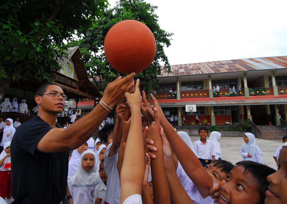 Mass Communication Specialist 3rd Class Matthew Jackson Teaches Children How to Spin a Basketball on Their Fingertip