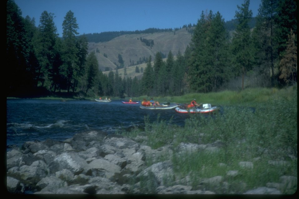 A large river being used by rafters for recreational use.