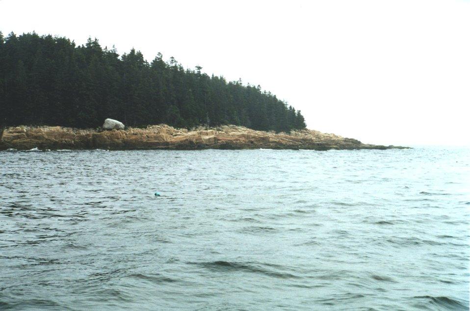 Glacial erratic boulder (white boulder in left center) trapped on eroding granite shoreline.