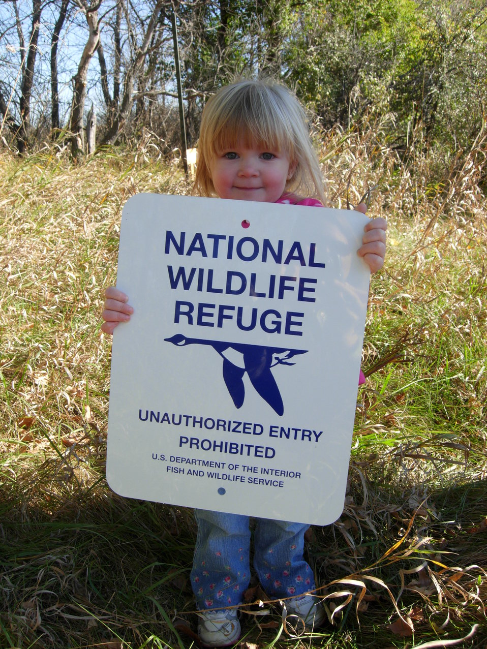 Girl Holding National Wildlife Refuge Sign