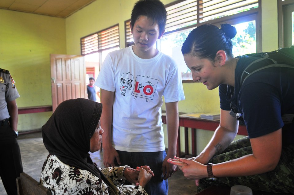 Canadian Air Force Lt. Rebecca Sparkes Screens an Indonesian Woman for Arthritis