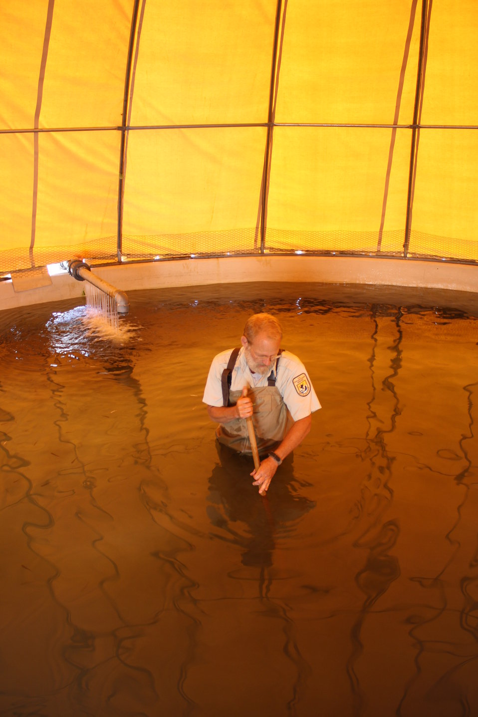 USFWS biologist cleans circular fish rearing pool of sediment
