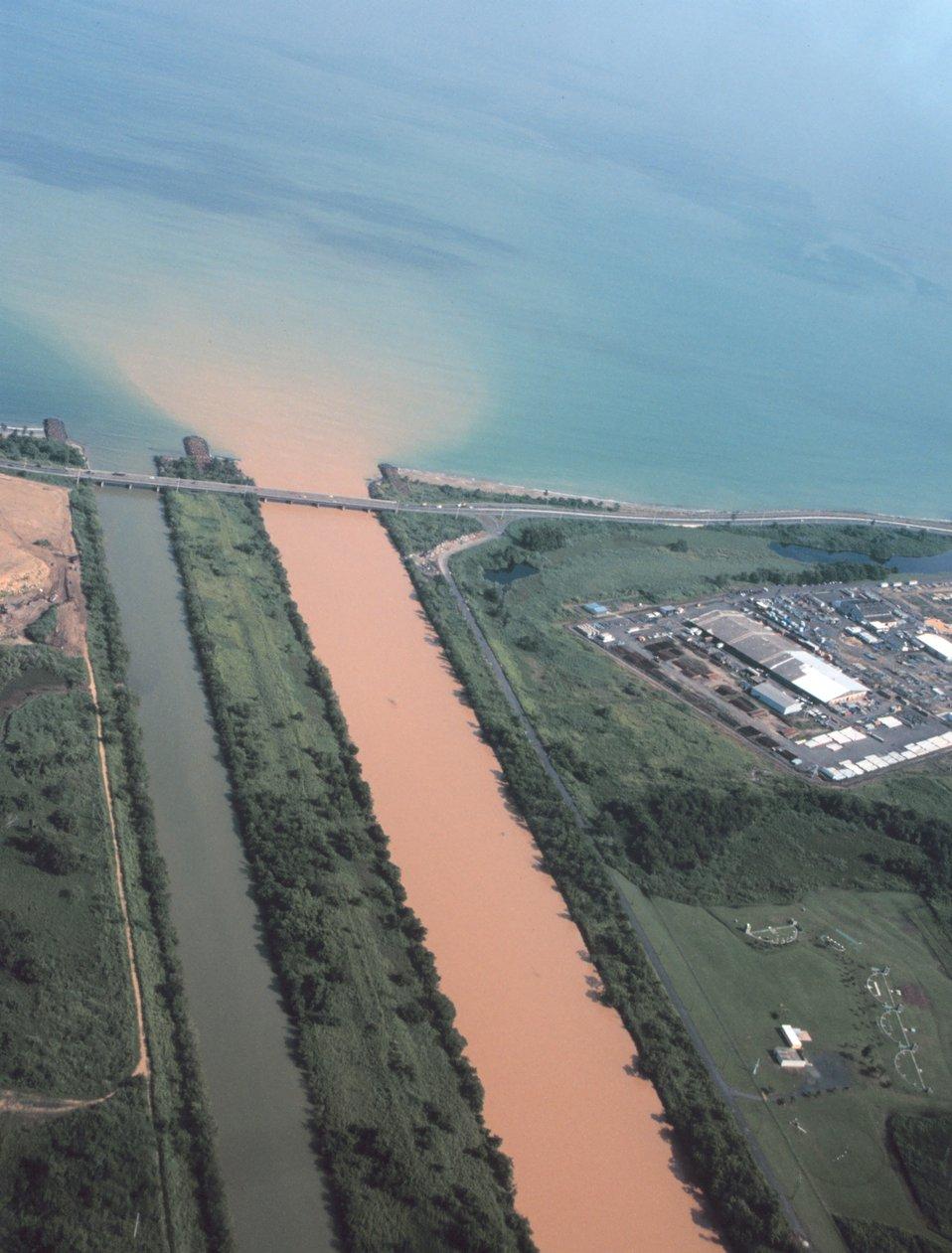 A heavily silted river enters the ocean near San Juan