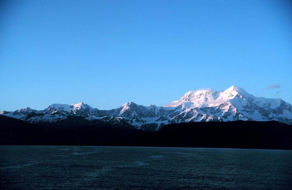 Photo #16 of Mount St. Elias sequence. Mount Saint Elias is one of the largest mountains visible from the sea on the North American continent.  It rises to a height of 18,008 feet in a distance of less than 20 miles from sea level at Icy Bay.