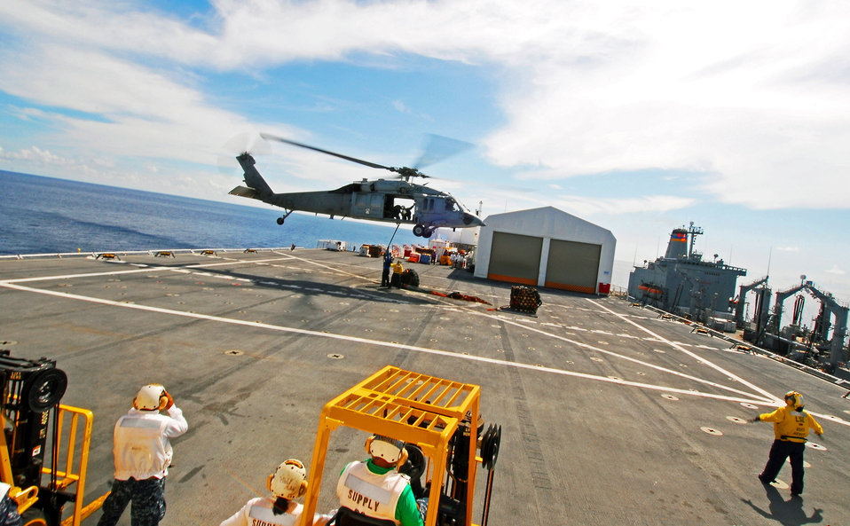 Flight Deck Members Attach Cargo to an MH-60S Knighthawk Helicopter