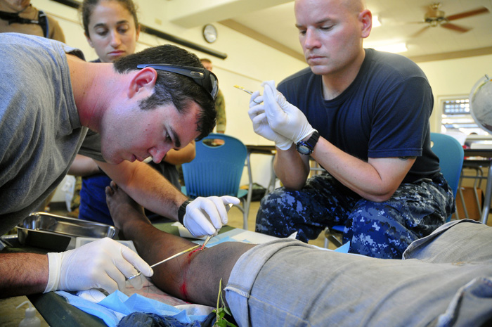 Australian Able Seaman Pearson, Lt. Bloir, and Project HOPE Volunteer Taylor Put Stiches in a Micronesian Boy's Leg