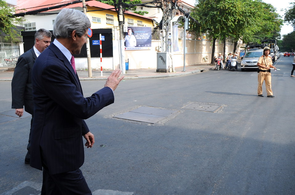 Secretary Kerry Waves to Vietnamese Policeman Walking Through Ho Chi Minh City