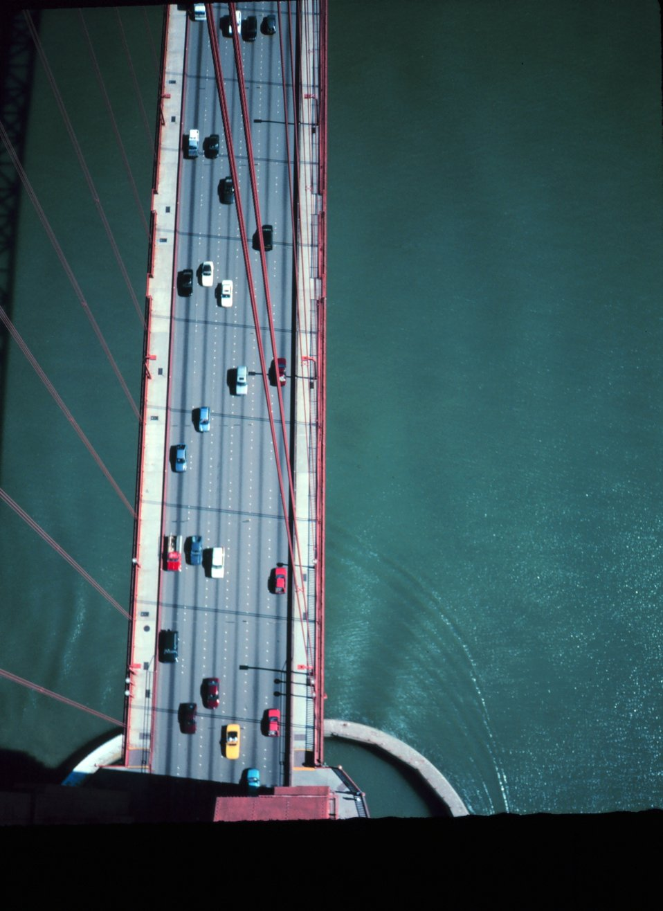 View from the top of the south tower of the Golden Gate Bridge looking down onto  the deck of the bridge.  The surface of the water is more than 700 feet below.