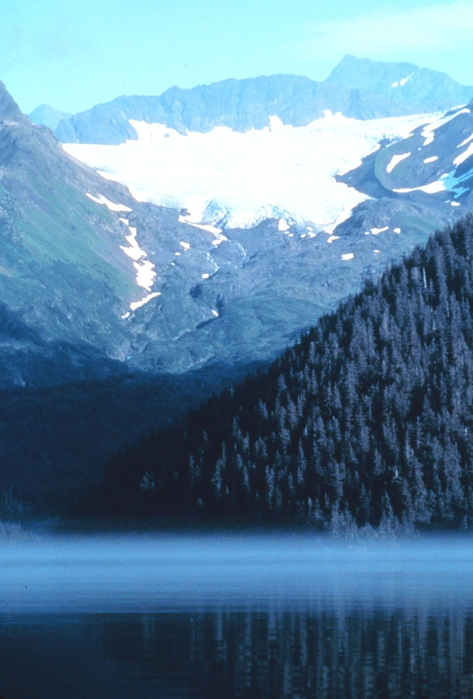 Mist below and glacier above while a high rocky peak dominates all.