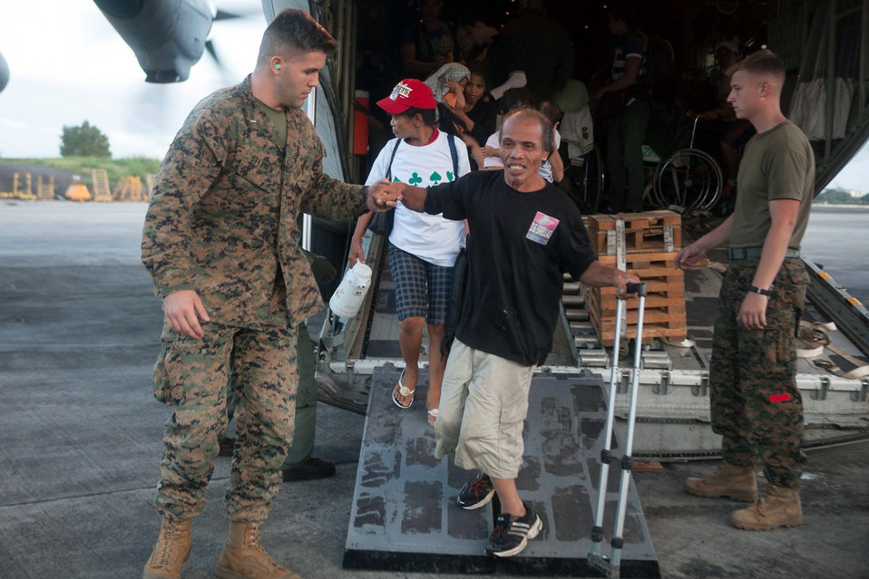A U.S. Marine Helps Displaced Civilians Transfer From Areas Affected by Typhoon Haiyan