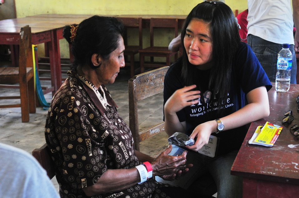 Project HOPE Nurse Ivana Winata Hands an Indonesian Woman a Pair of New Glasses
