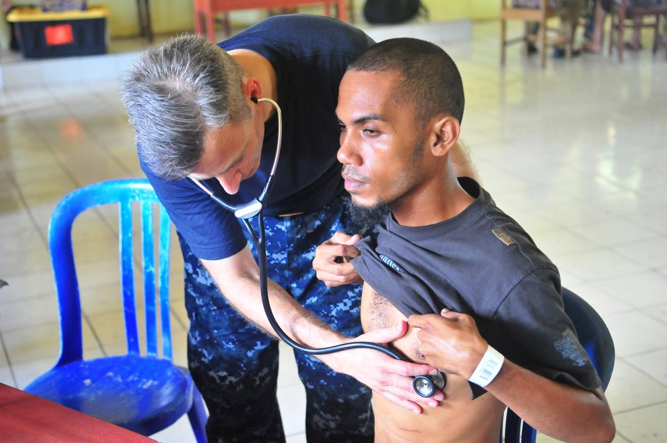 Lt. Cmdr. (Dr.) Ira Nash Listens to an Indonesian Man's Heartbeat