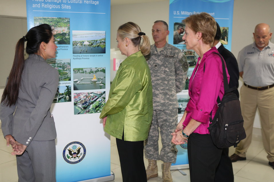 Secretary Clinton, With Ambassador Kenney, Looks at a Presentation of Flood Damage