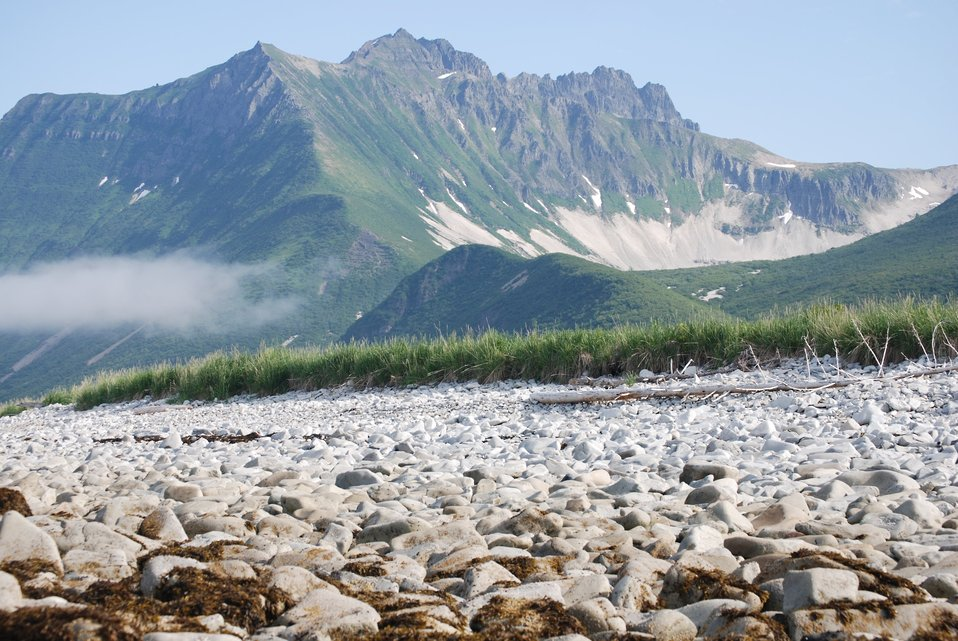 Looking over a boulder beach to rugged mountains of the Alaska Peninsula. Dakavak Bay.