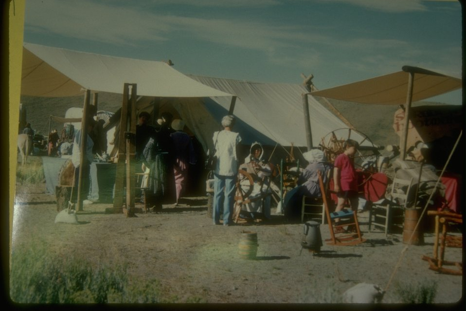 A cultural event replicating an old camp site in the middle of the rangeland.  It looks like a tent city.  People are dressed as pioneers showing old chairs, spinning wheels, and other exhibits.
