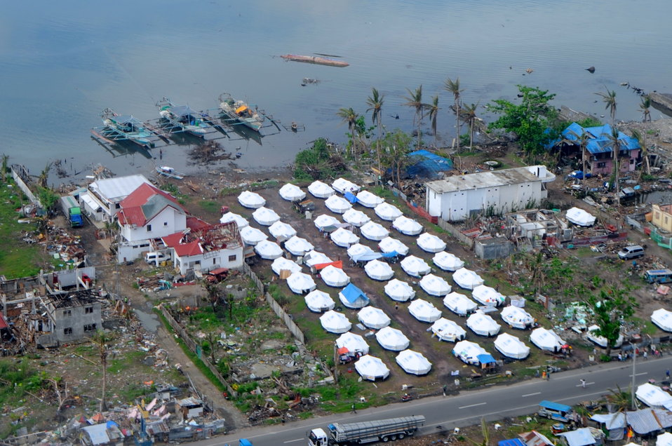 Temporary Shelters Sit Beside Lingering Damage as Secretary Kerry Arrives in Tacloban City