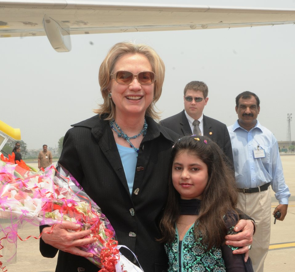 A Young Girl Attired in Pakistani National Dress Presents a Bouquet to Secretary Clinton
