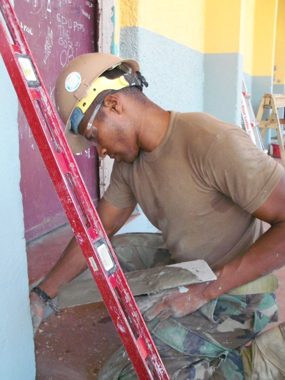 Builder 3rd Class Williams Spreads a Thin Layer of Plaster Outside of the Classroom Walls