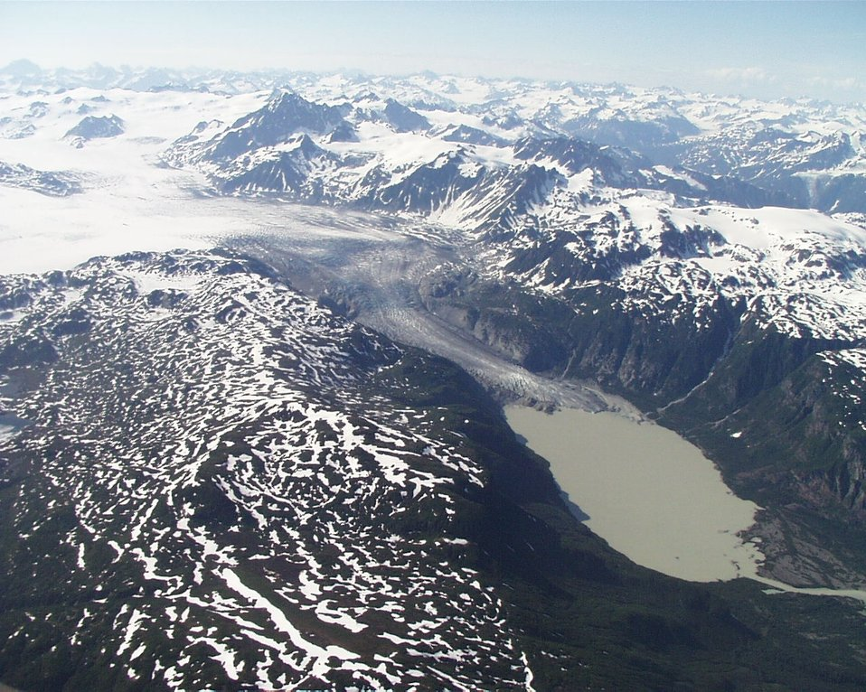 Aerial view of glacier and mountains.  Glacier melting into terminal lake with river outflowing to righ