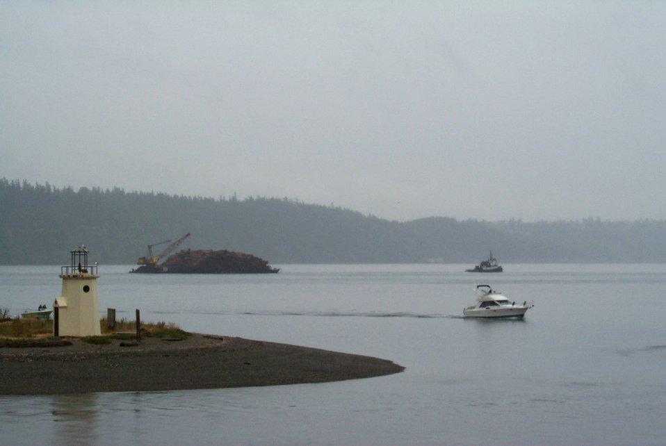Looking past the spit at Gig Harbor to a barge-load of pine bark headed for to Steilacoom.
