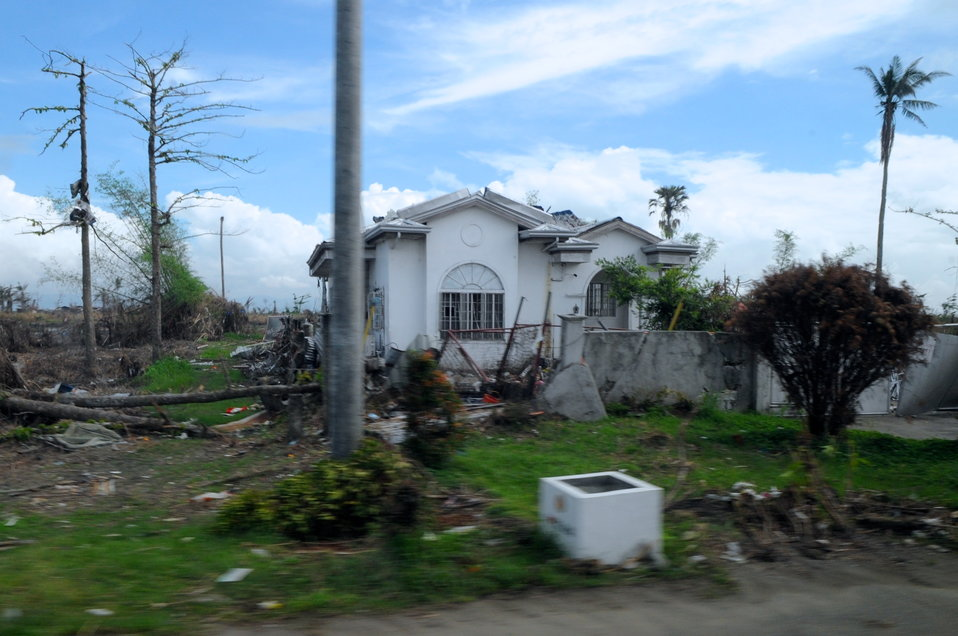 Secretary Kerry's Vehicle Passes a Home Damaged by Typhoon Haiyan