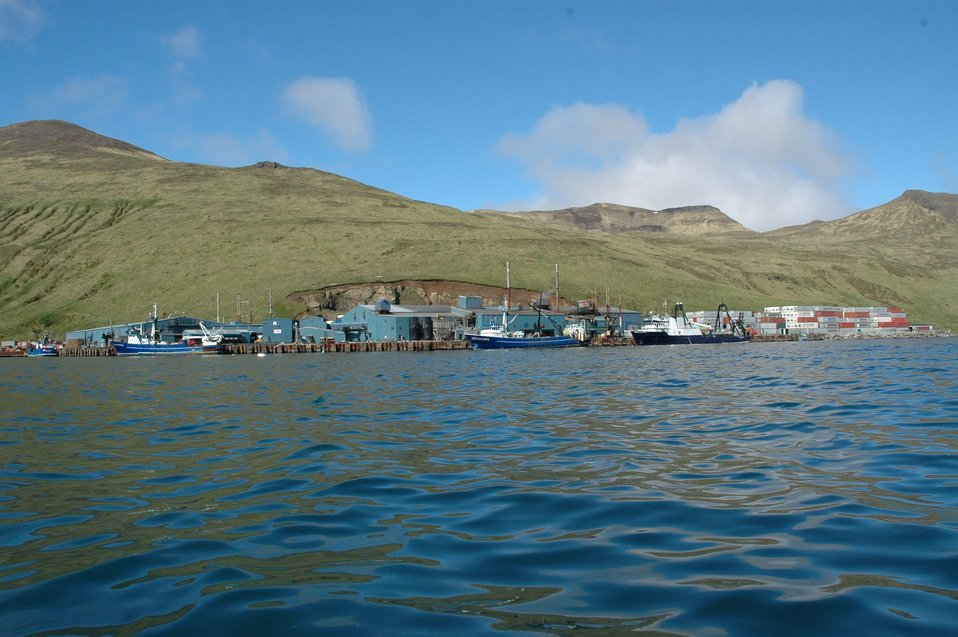 Fishing boats and stacked containers at Akutan Harbor