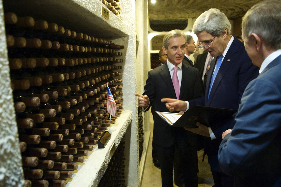 Secretary Kerry Examines a Certificate as the Moldovans Designate a Bin of Wine in His Honor
