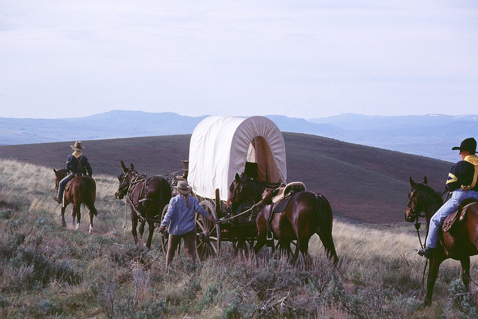 NHOTIC 10th Anniversary, wagon train reenactment. Pioneers, covered wagons, and soldiers on horseback on the Oregon Trail.