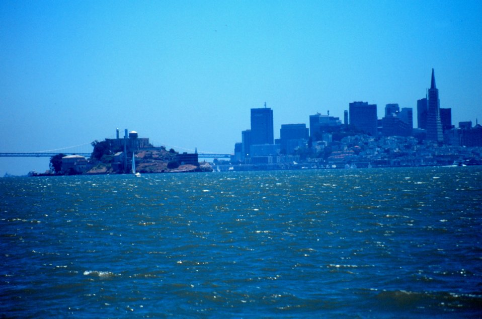 Alcatraz Island, the Oakland Bay Bridge,  and the San Francisco skyline as seen from a small boat looking south.