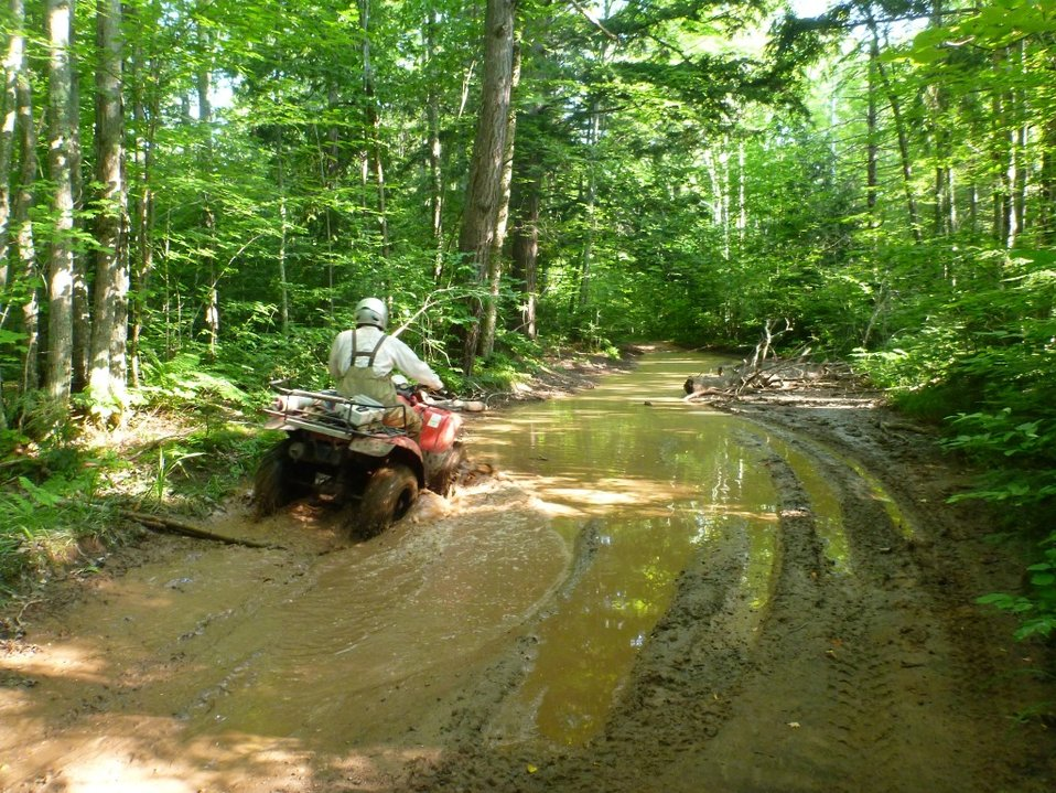 Service Employee Alex Carter ATVing to a remote larval assessment site at the West Sleeping River, Michigan.