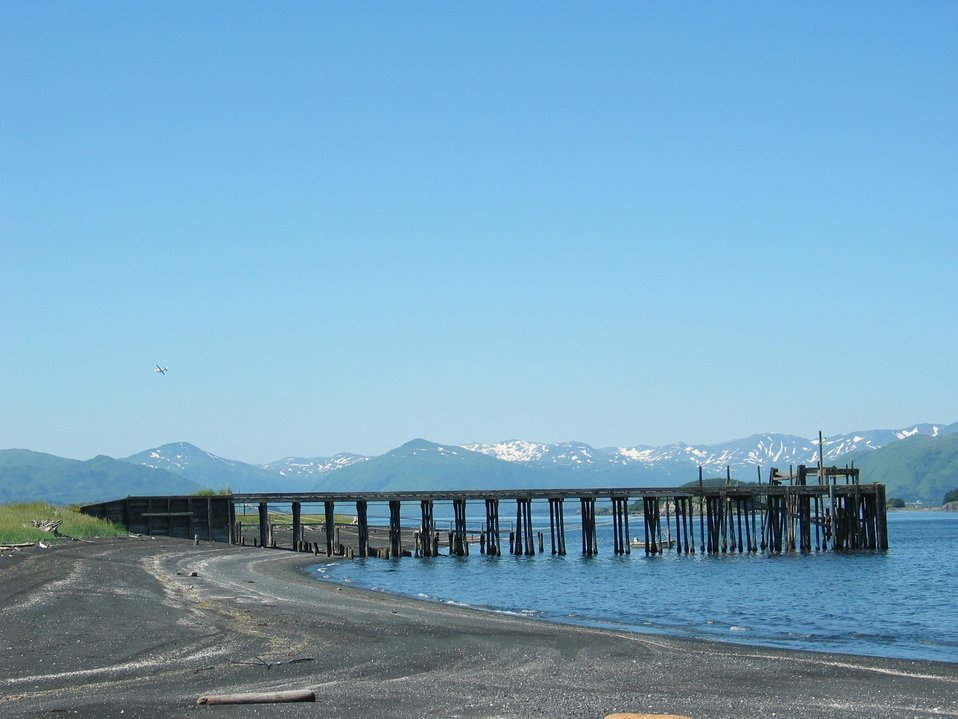 Black sand and cobble beach on Kodiak Island with pier at low tide. Alaska Peninsula mountains are seen in background.