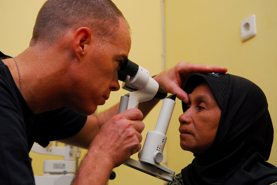 Cmdr. (Dr.) Kent Blade Examines a Patient's Eye