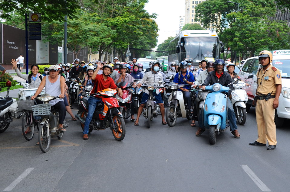Vietnamese Motorbike Riders Pause as Secretary Kerry Crosses Street