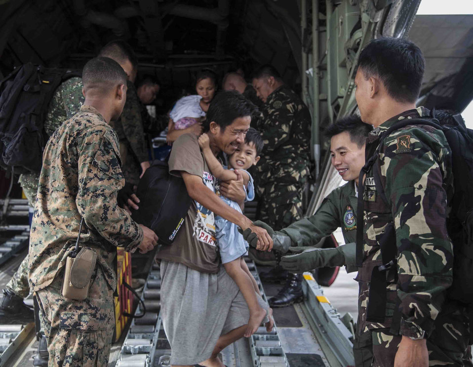 U.S. Marine Corps Cpl. Cannon and Members of the Philippine Armed Forces Help People Displaced by Typhoon Haiyan