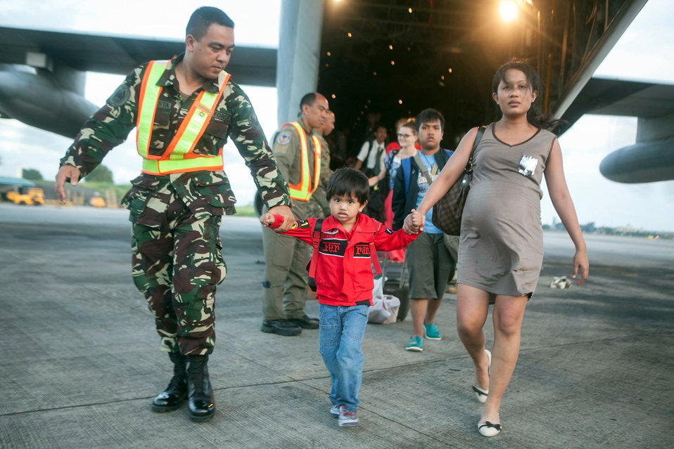 A Filipino Airman Offloads Civilians