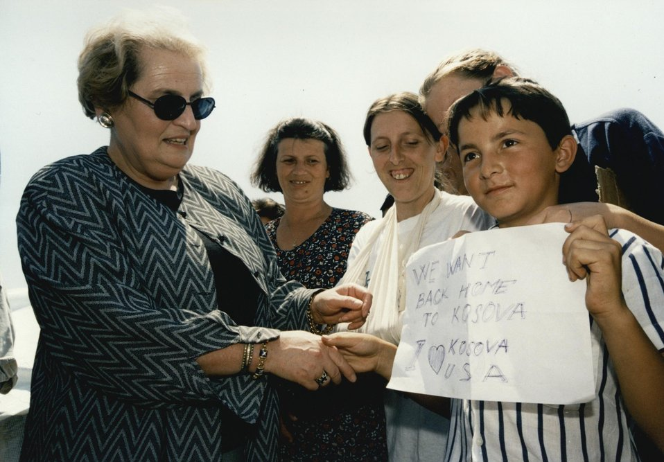 U.S. Secretary of State Madeleine Albright greets boy holding sign that reads: 'We want back home to Kosova.'