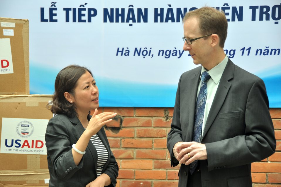 Dr. Nguyen Thu Thuy, Deputy Director General, Department of Animal Health, talks to USAID Mission Director Joakim Parker at the personal protective equipment handover ceremony.
