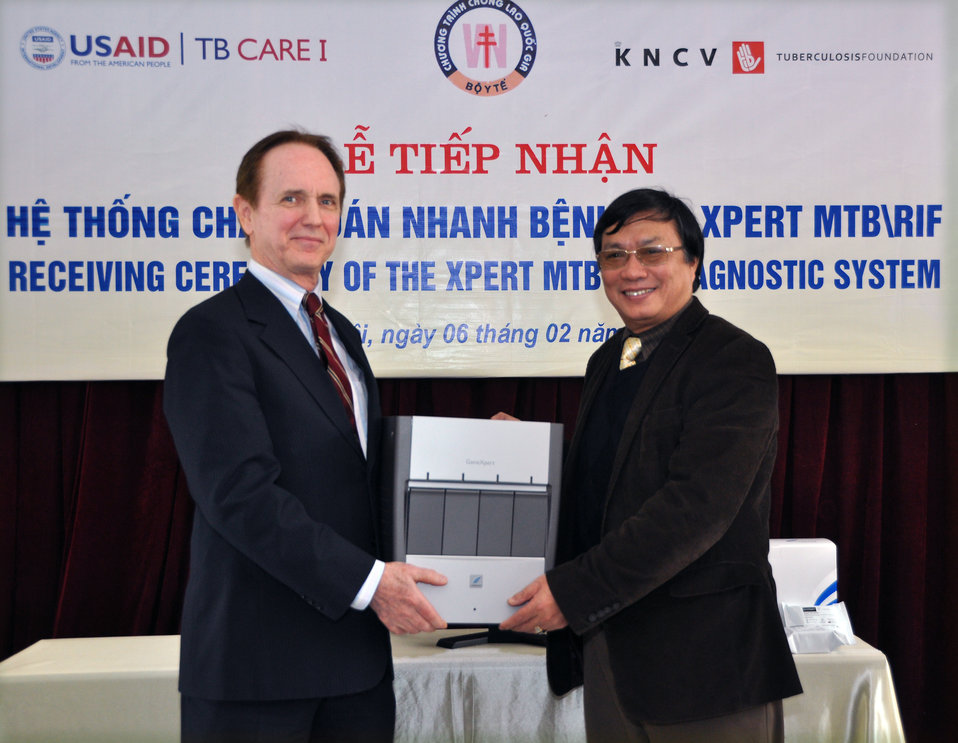 Prof. Dr. Dinh Ngoc Sy, manager of Vietnam's National TB Control Program (right), receives an Xpert Testing System from USAID Mission Director, Francis Donovan.