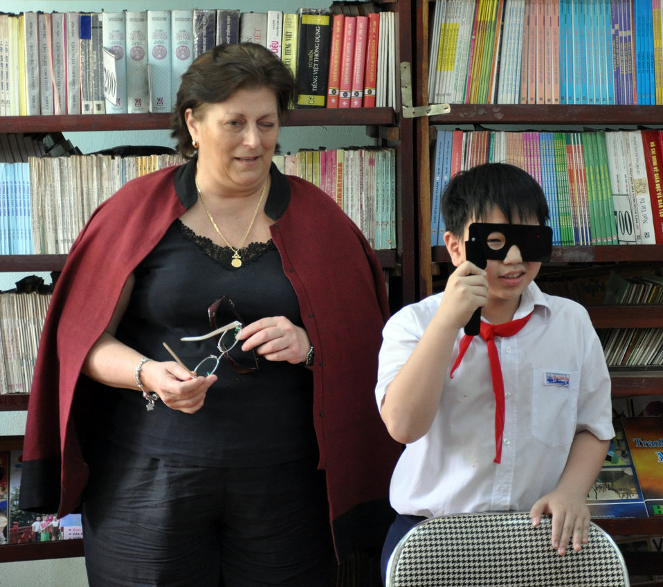 U.S. Embassy Charge d'affaires Claire Pierangelo attends eye screening at Phan Dinh Phung Primary School